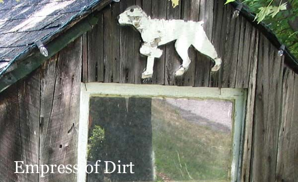 Wood cutout of a white dog hanging on a rustic old shed.