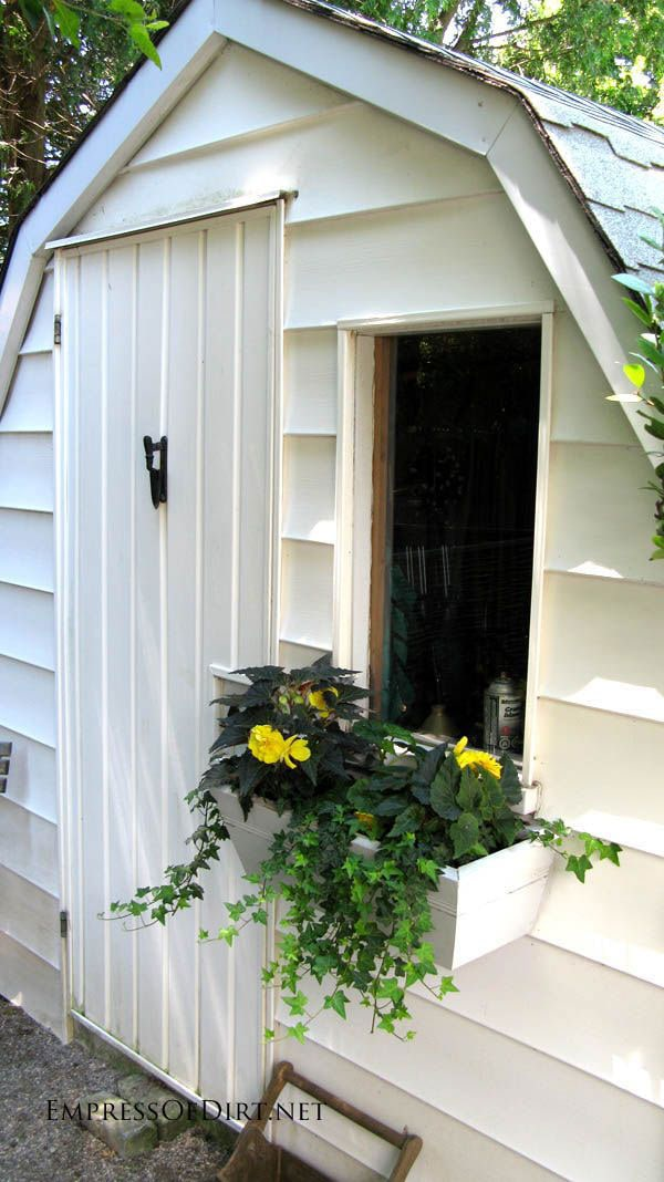 Creative DIY garden container ideas - White shed with window box and flowers