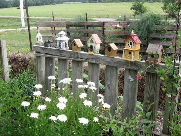 Colourful birdhouses on a fence | Gallery of Creative Birdhouse Ideas at empressofdirt.net